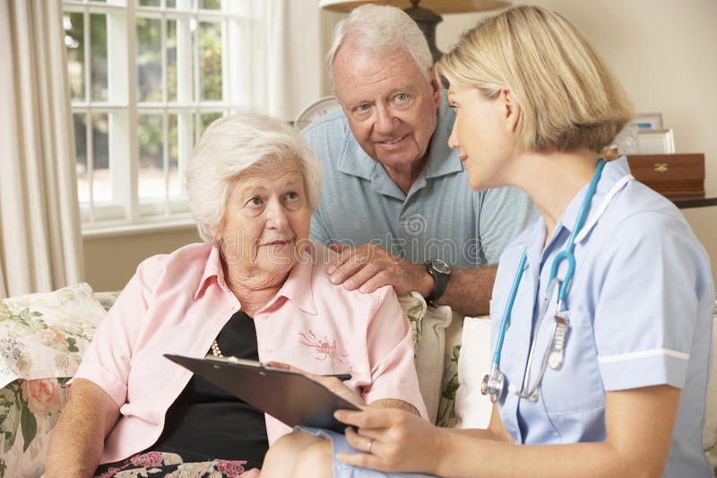 Pensionerad hög kvinna som har den vård- kontrollen med sjuksköterskan At Home arkivfoton