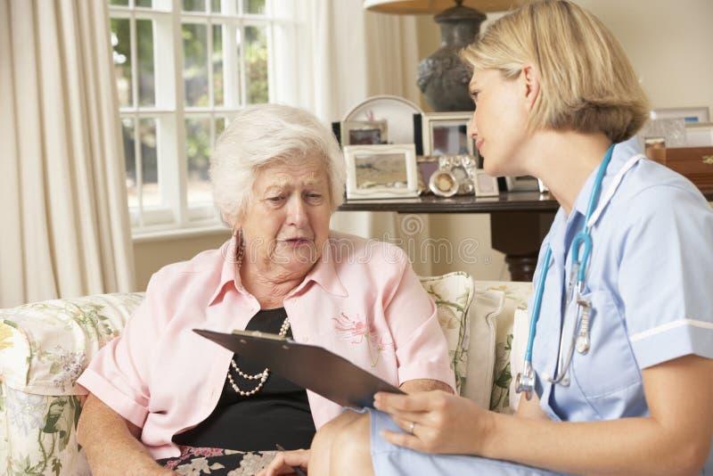 Pensionerad hög kvinna som har den vård- kontrollen med sjuksköterskan At Home arkivfoto