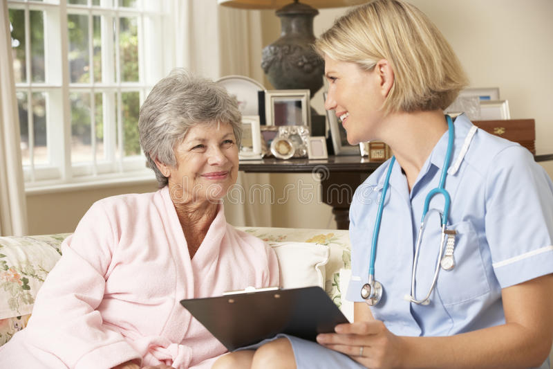 Pensionerad hög kvinna som har den vård- kontrollen med sjuksköterskan At Home royaltyfri fotografi
