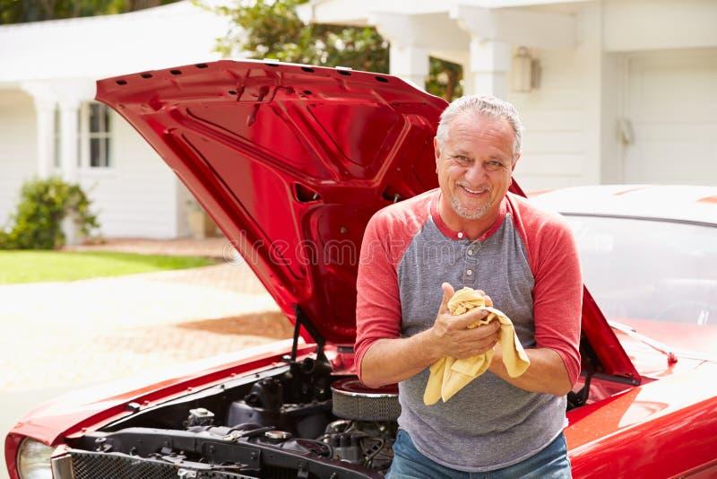 Pensionerad hög man som arbetar på den återställda klassiska bilen arkivfoto
