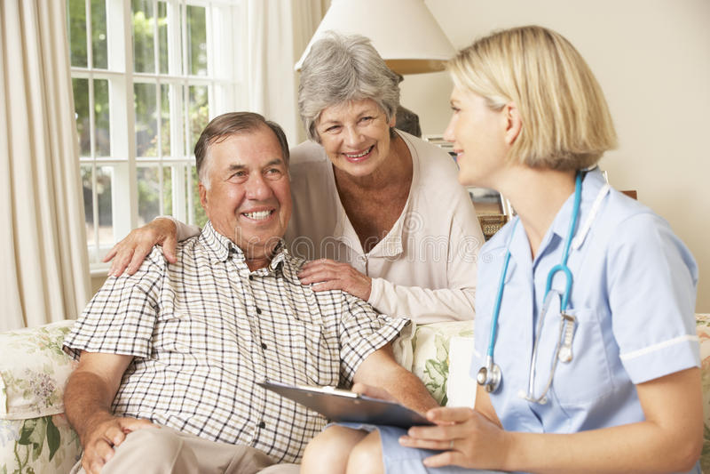 Pensionerad hög man som har den vård- kontrollen med sjuksköterskan At Home arkivbild