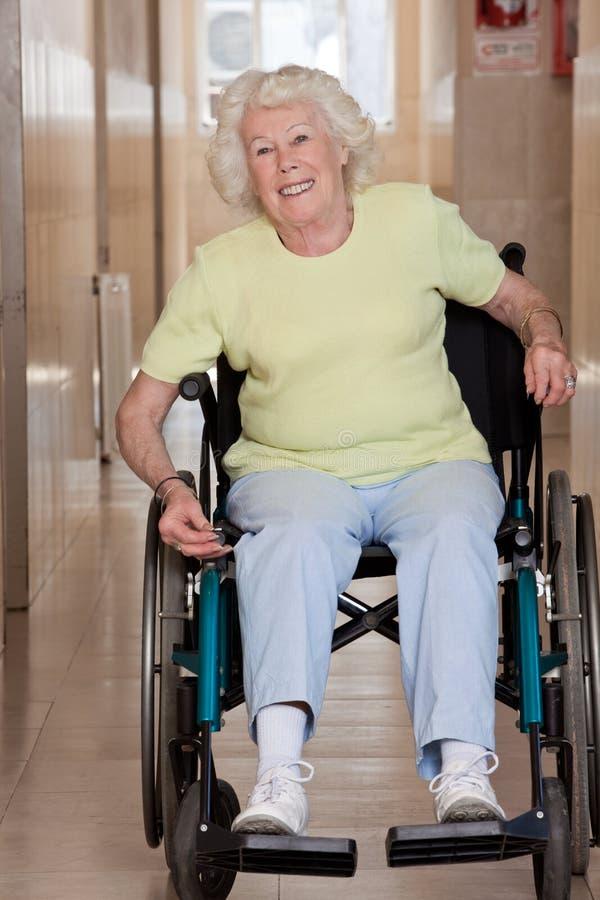 Pensionerad kvinna på rullstolen royaltyfri bild