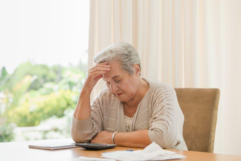 Pensionerad kvinna som beräknar henne inhemska bills royaltyfri foto