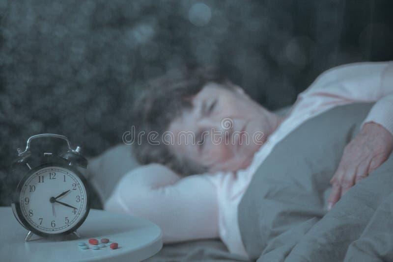 Pensionerad kvinna som har sömnproblem arkivfoto