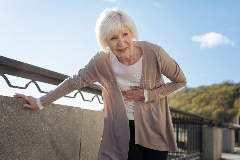 Pensionerad kvinnakänsla smärtar under promenaden royaltyfria bilder