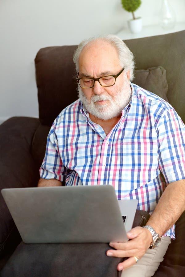 Pensionerad man med sammanträde för vitt skägg i hans hem fotografering för bildbyråer