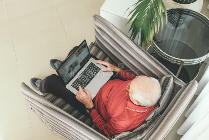 Pensionerad man som hemma använder datatekniker royaltyfri bild