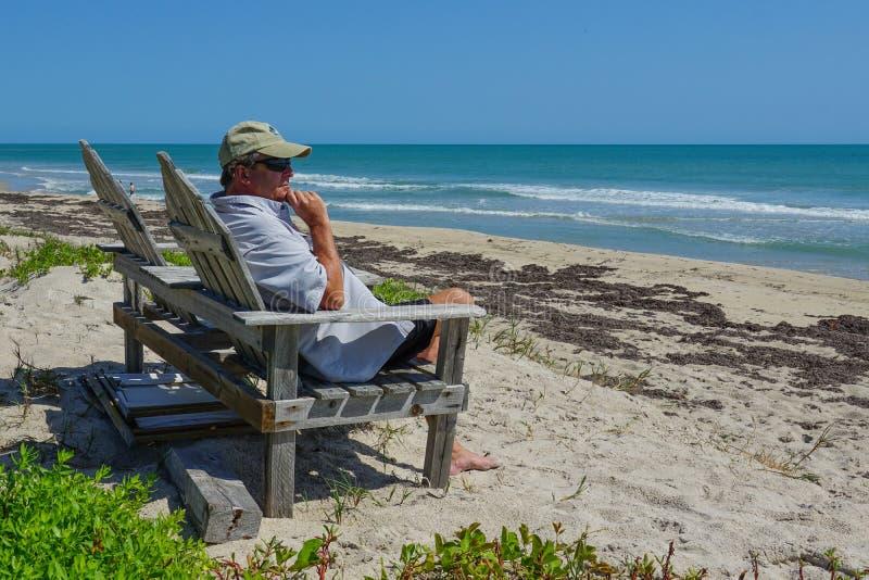 Pensionerad man som sitter på en stol som förbiser det turkosblåa havet arkivfoto