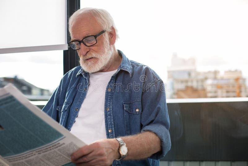 Pensionerad skäggig gentleman som beskådar ny information i tidning royaltyfri fotografi