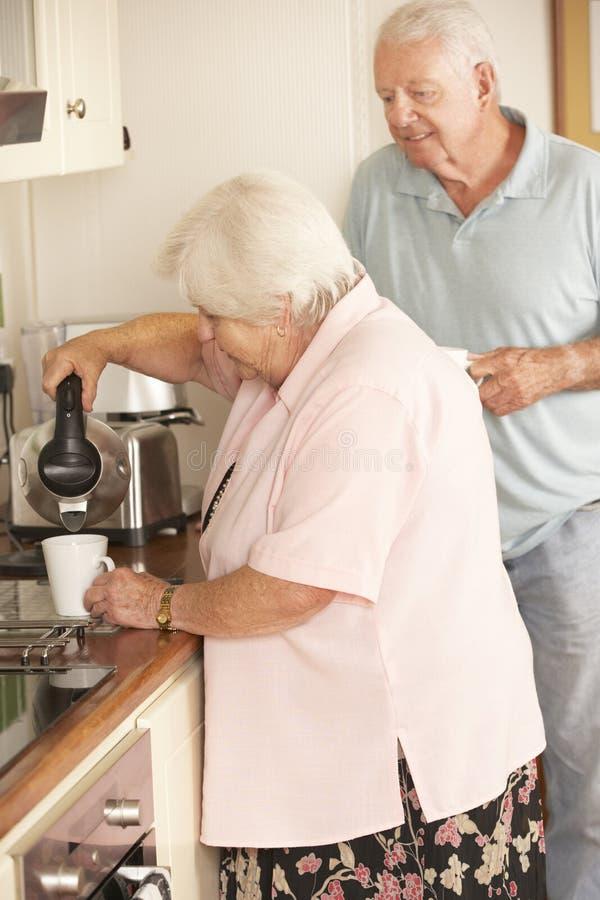 Pensionerade höga par i kök som tillsammans gör den varma drinken royaltyfria bilder