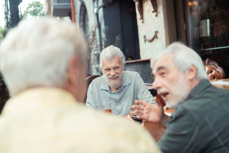 Pensionerade män som talar och dricker alkoholyttersidan arkivbild