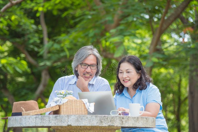 Pensionerade par som använder bärbar datordatoren parkerar in royaltyfri foto