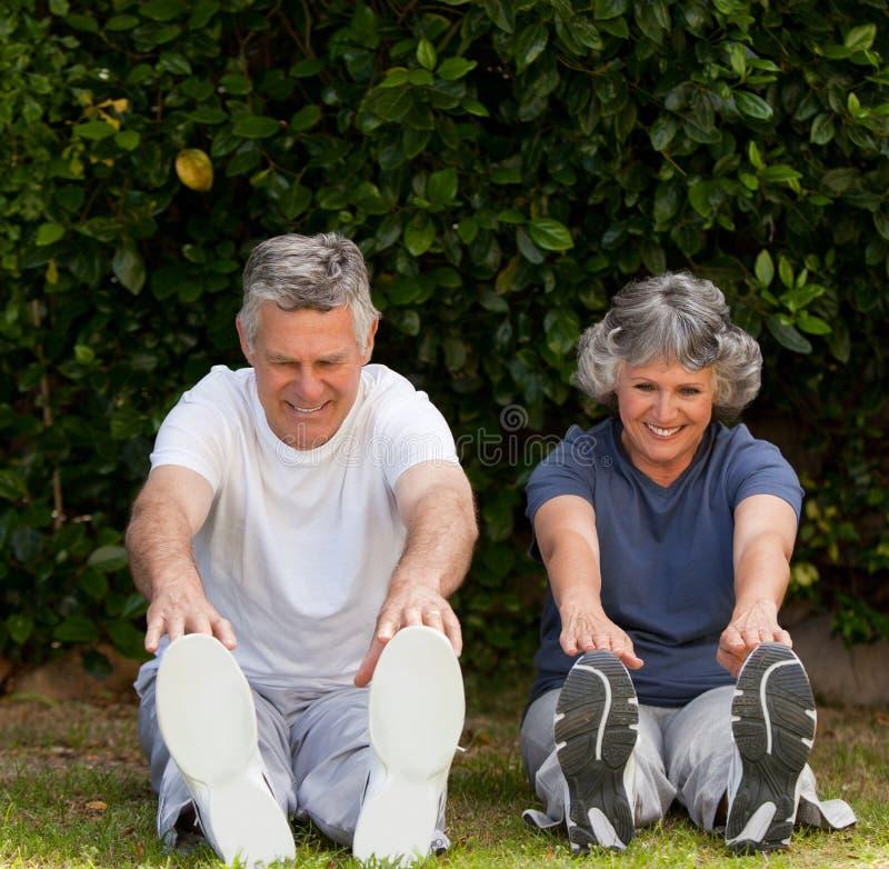 Pensionerade par som gör deras övningar arkivbilder