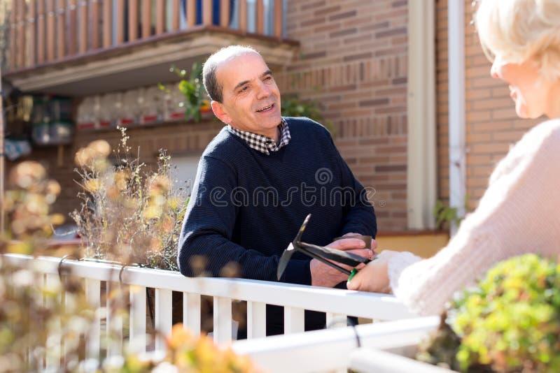 Pensionerade par som talar i uteplats arkivbild