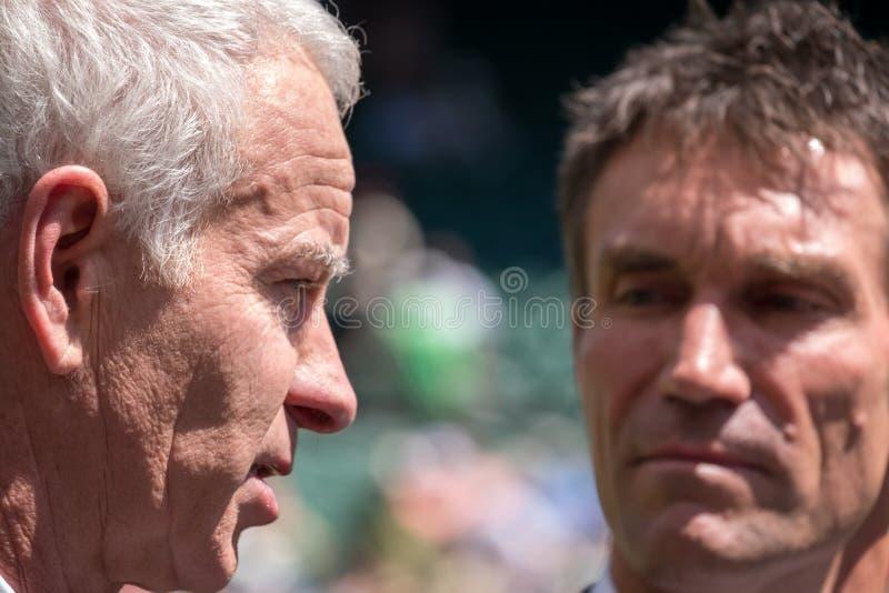 Pensionerade spelare, Pat Cash och John McEnroe i konversation för starten av finalerna för man` s på mittdomstolen royaltyfria bilder