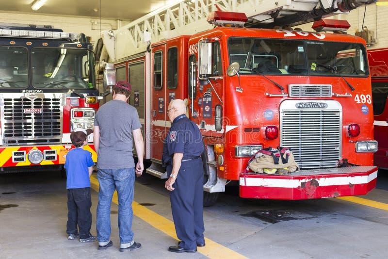 Pensionerat brandmananseende med fadern och sonen som besöker brandstationen arkivfoton