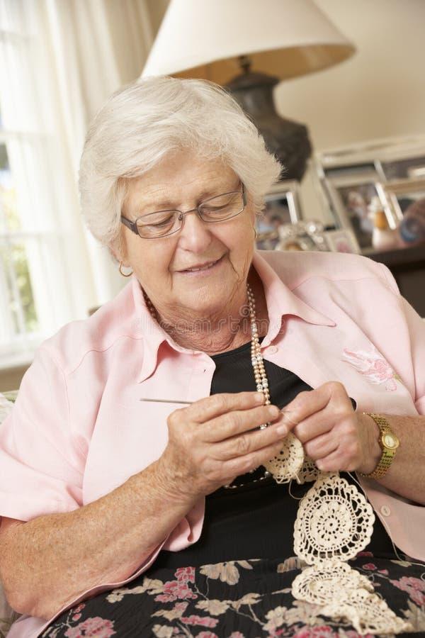 Pensionerat högt kvinnasammanträde på Sofa At Home Doing Crochet royaltyfri fotografi