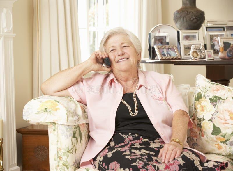 Pensionerat högt kvinnasammanträde på Sofa At Home On Phone arkivfoto