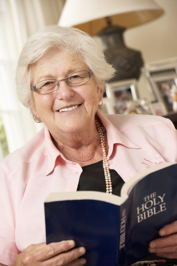 Pensionerat högt kvinnasammanträde på Sofa At Home Reading Book royaltyfri bild