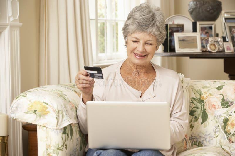 Pensionerat högt kvinnasammanträde på Sofa At Home Using Laptop som gör online-köpet arkivbilder