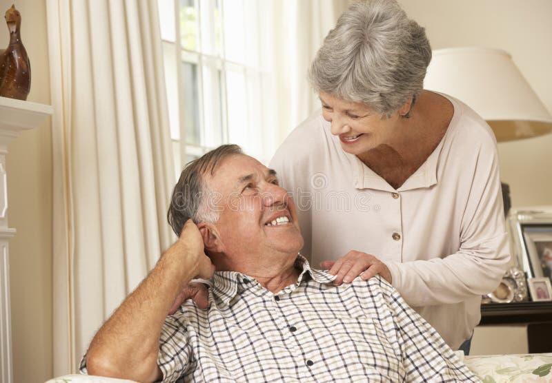Pensionerat högt parsammanträde på Sofa At Home Together royaltyfria bilder