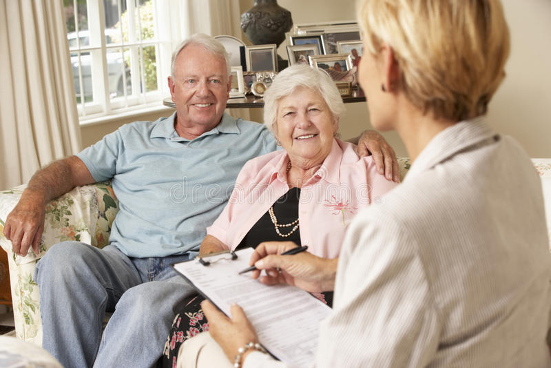 Pensionerat högt parsammanträde på Sofa Talking To Financial Advisor royaltyfria bilder