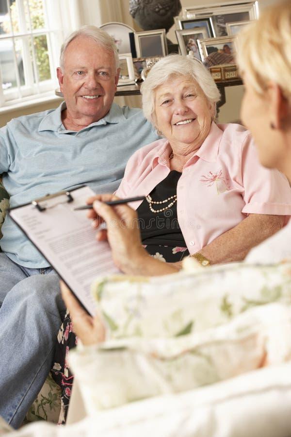 Pensionerat högt parsammanträde på Sofa Talking To Financial Advisor arkivbilder