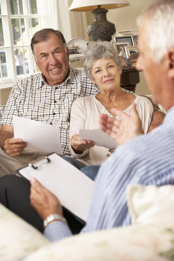 Pensionerat högt parsammanträde på Sofa Talking To Financial Advisor royaltyfri fotografi