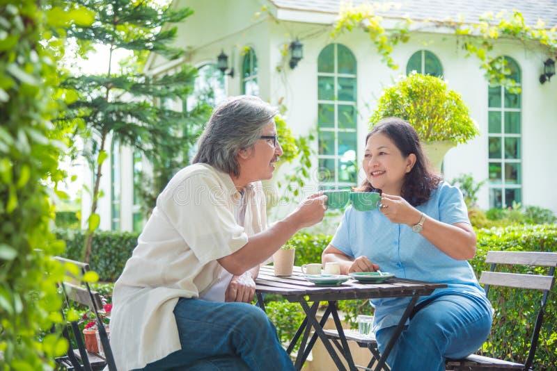 Pensionerat parsammanträde i trädgårds- och dricka kaffe arkivfoto