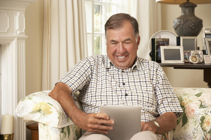 Pensionerat sammanträde för hög man på den Sofa At Home Using Tablet datoren arkivbilder