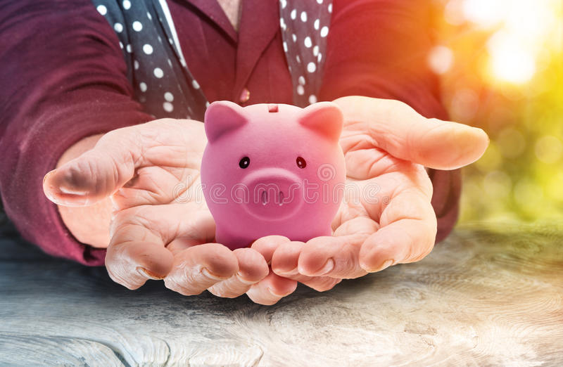 Pensioneringsconcept - Bejaarde Dame Holding een Spaarvarken bij Zonsondergang stock foto's