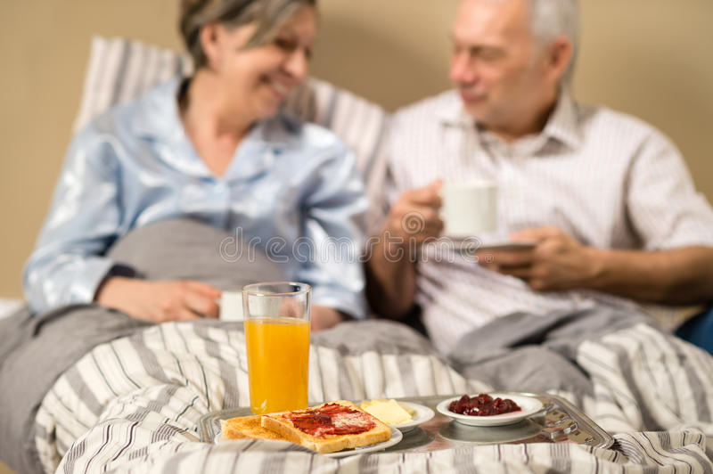 Pensioners drinking coffee in the bed royalty free stock photos