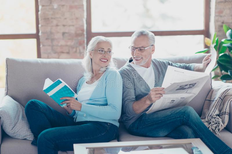 Pensioners are resting and relaxing while reading book and newspaper. They are sitting on a sofa and smiling to each other stock image
