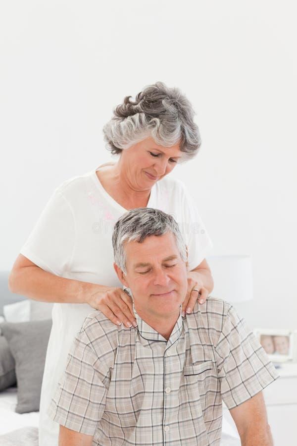 Pensionierte Frau, die ihrem Ehemann eine Massage gibt lizenzfreie stockfotografie