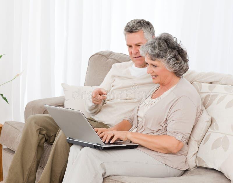 Pensionierte Geliebte, die ihren Laptop betrachten lizenzfreie stockbilder