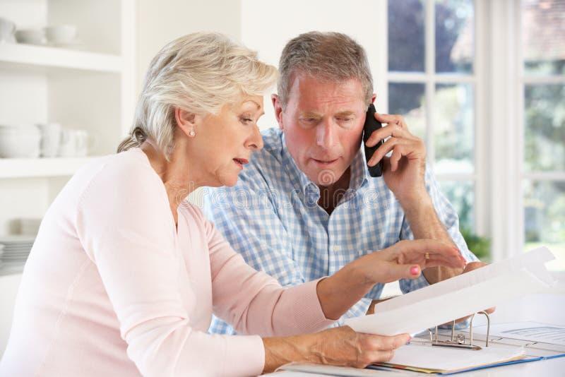 Pensionierte Paare mit Haushaltsrechnungen lizenzfreies stockbild