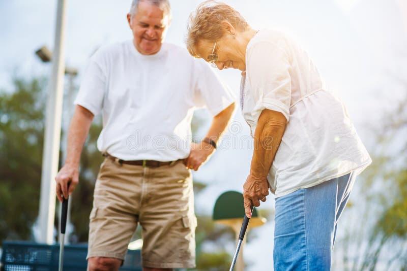 Pensionierter Lebensstil von den älteren Paaren, die Minigolf spielen lizenzfreie stockfotos