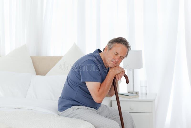 Pensionierter Mann mit seinem gehenden Steuerknüppel lizenzfreie stockfotografie