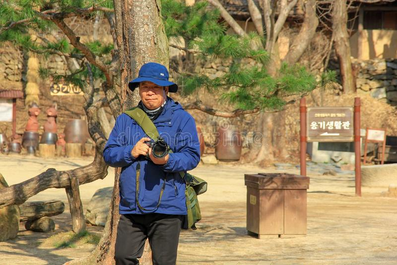 Pensioniertes volles Gesicht des älteren koreanischen Mannes, das eine Kamera im Volksdorfvorfrühling Minsokchon, Yongin, Südkore stockbilder