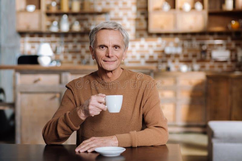 Pensionista alegre calmo que sorri ao sentar-se com um copo do quando fotografia de stock