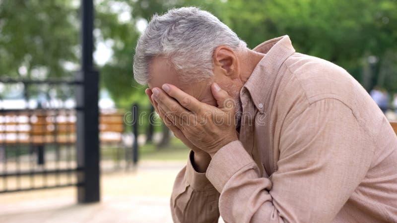 Pensionista desesperado que grita, cobrindo os olhos pelas mãos, perda de sofrimento, problema foto de stock royalty free