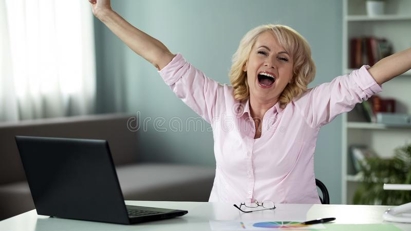 Pensionista fêmea feliz ganhar na competição criativa da ideia, senhora bem sucedida imagem de stock royalty free