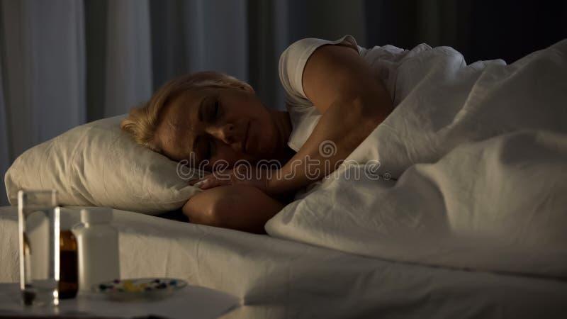 Pensionista fêmea que dorme na cama, nos comprimidos e no vidro da água perto da tabela, doença fotos de stock