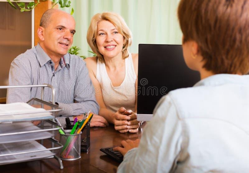 Pensionista felizes que falam com gerente fotografia de stock royalty free