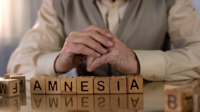 Pensionista idoso que faz a amnésia de cubos de madeira na tabela, cuidados médicos da palavra fotos de stock