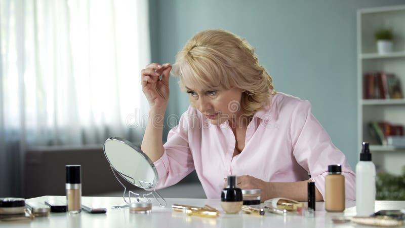 Pensionista louro fêmea que olha o cabelo no espelho, processo de envelhecimento, pontas da beleza foto de stock