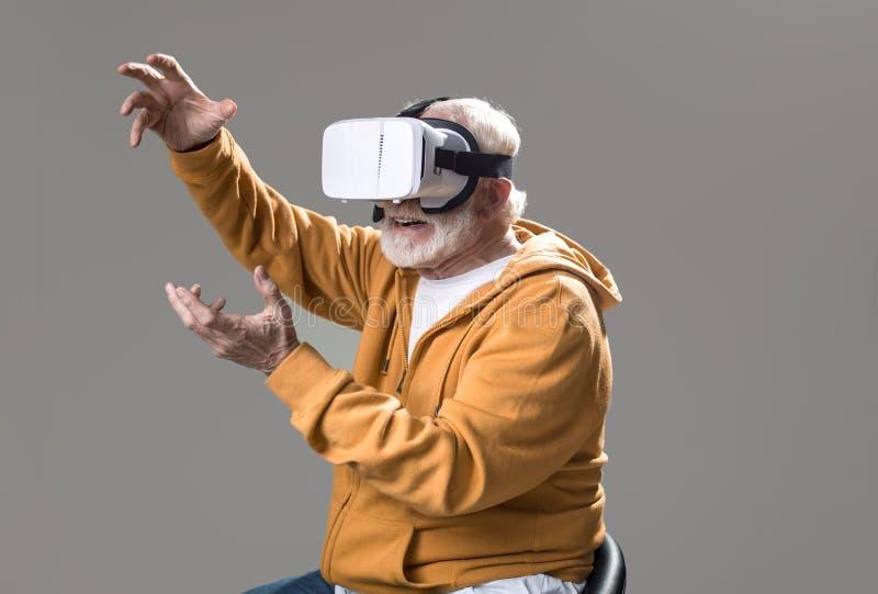 Pensionista masculino alegre que usa los vidrios virtuales fotografía de archivo libre de regalías