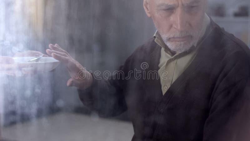 Pensionista masculino presionado que rechaza comer las gachas de avena, sintiendo solas en hospicio fotos de archivo