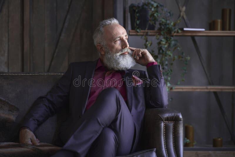Pensionista não barbeado pensativo que situa no apartamento imagem de stock