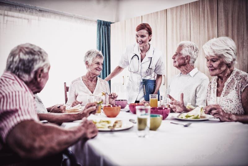Pensionista no almoço com enfermeira fotografia de stock